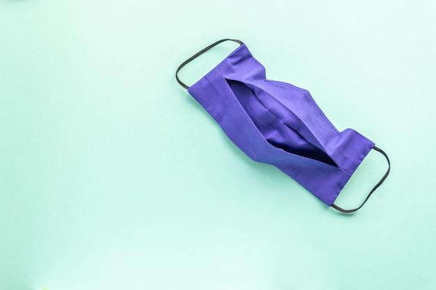 Ciemnoniebieska maska wielokrotnego użytku na miętowym gładkim tle. miejsce na tekst. lekarstwo.