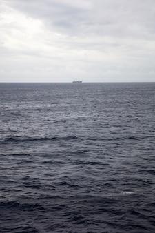 Ciemnoniebieska powierzchnia wody na głębokim morzu ze statkiem na odległym horyzoncie