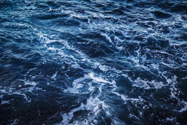 Ciemnoniebieska woda morska z białym piankowym widokiem z góry