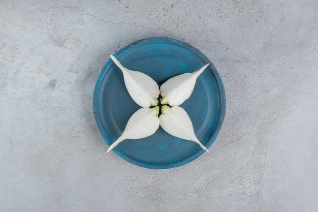 Ciemnoniebieski talerz z czosnkiem na szarym tle. zdjęcie wysokiej jakości