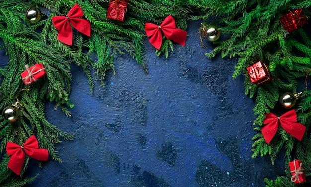Ciemnoniebieskie tło pustej przestrzeni. gałęzie choinkowe i dekoracje.