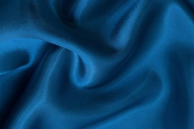 Ciemnoniebieskie tło tekstury tkaniny, zmięty wzór jedwabiu lub lnu.