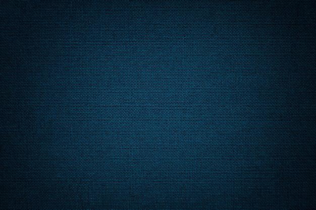 Ciemnoniebieskie tło z materiału tekstylnego. materiał o naturalnej fakturze. zasłona.