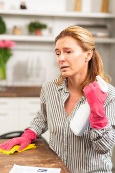 Ciemnooka dojrzała kobieta czuje się naprawdę chora sprzątając mieszkanie podczas alergii