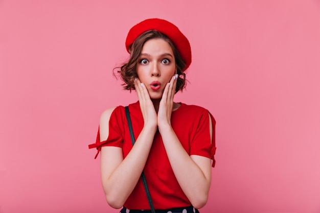 Ciemnooka francuzka wyrażająca zdumienie. portret zdziwiona czarująca dziewczyna w czerwonym berecie.