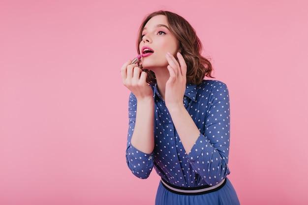 Ciemnooka ładna europejska dama robi makijaż z otwartymi ustami. miła kręcona dziewczyna w niebieskich ubraniach przy użyciu różowej szminki.