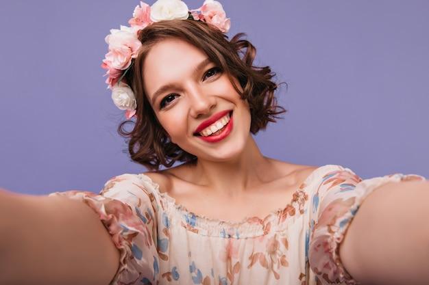 Ciemnooka śliczna kobieta w wieńcu dokonywanie selfie z uśmiechem. blithesome biała dziewczyna ze stawiającymi krótkie kręcone włosy.