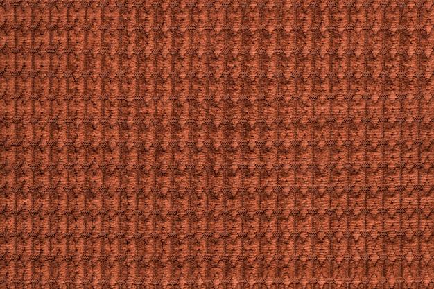 Ciemnopomarańczowe tło z miękkiej wełnistej tkaniny z bliska. tekstury makro tkanin