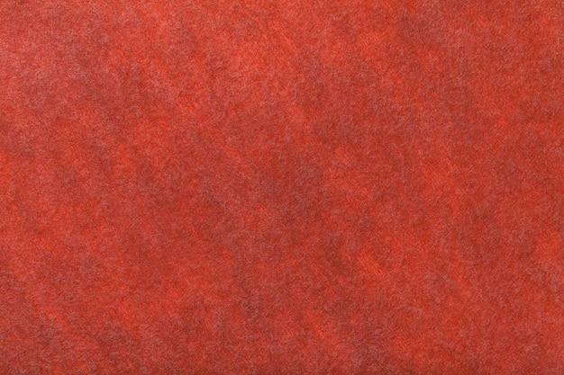 Ciemnopomarańczowy matowy zamszowy zbliżenie tkaniny. aksamitna faktura filcu.