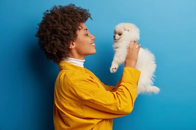 Ciemnoskóra dama z zaokrąglonymi ustami, chce pocałować uroczego zwierzaka, bawi się małym szczeniakiem