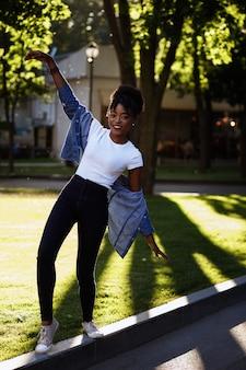 Ciemnoskóra dziewczyna bawi się w parku w lecie