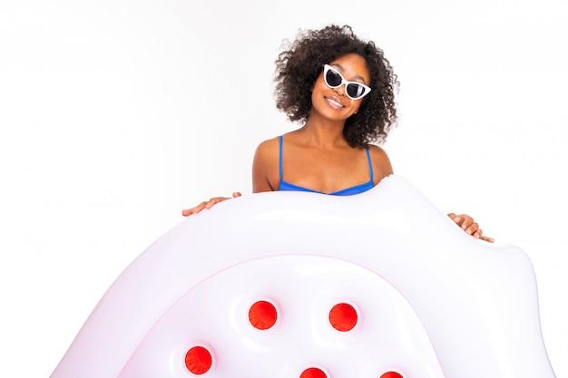 Ciemnoskóra dziewczyna w okularach przeciwsłonecznych i kostiumie kąpielowym na białym tle, szeroki uśmiech z zębami w brunetce z kręconymi włosami