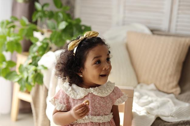 Ciemnoskóra dziewczyna zjada bajgla i się uśmiecha