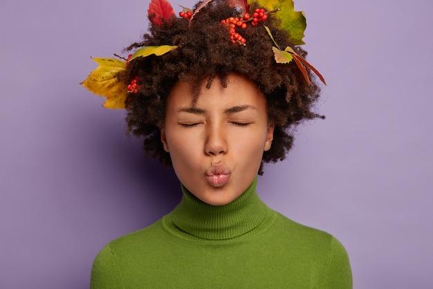 Ciemnoskóra kobieta ma zaokrąglone usta, zamyka oczy, głowę ozdobioną jesiennymi opadłymi liśćmi, ubrana w luźny strój