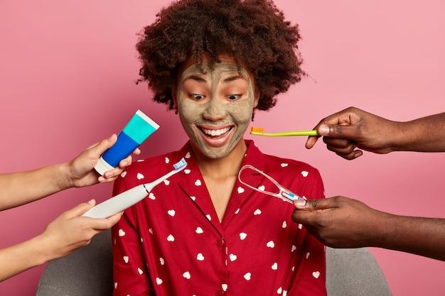Ciemnoskóra kobieta poddaje się leczeniu stomatologicznemu, dba o zęby, nosi czerwoną piżamę