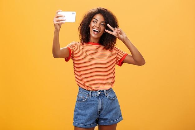 Ciemnoskóra kobieta robi selfie pokazując znak zwycięstwa na pomarańczowej ścianie