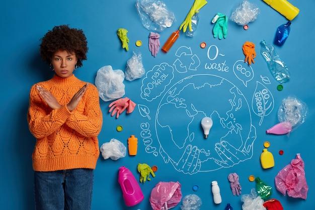 Ciemnoskóra kobieta trzyma ręce skrzyżowane na ciele, pokazuje gest zaprzeczenia, ratuje ziemię przed zanieczyszczeniem, stoi w pomieszczeniach, rysuje symboliczny obraz z okazji światowego dnia środowiska