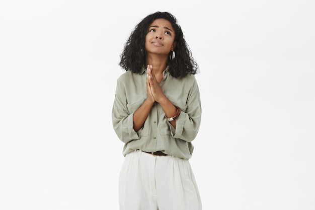 Ciemnoskóra kobieta trzymająca się za ręce w modlitwie patrząc w górę ze smutnym, wiernym spojrzeniem życzenia