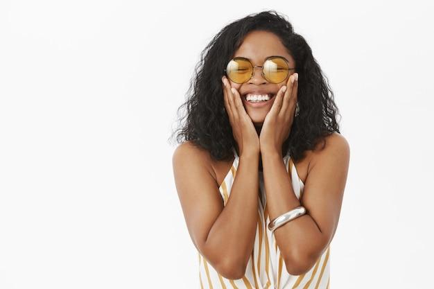 Ciemnoskóra kobieta, zamykająca oczy z radości i przyjemności, trzymająca dłonie na policzkach, uśmiechnięta szeroko