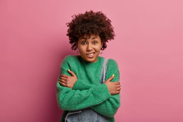 Ciemnoskóra kręcona kobieta jest bardzo zimna, krzyżuje ramiona na klatce piersiowej, drży od uczucia przemarznięcia, uśmiecha się na twarzy, nosi zielony sweter, odizolowana na różowej ścianie, spaceruje podczas chłodnej pogody