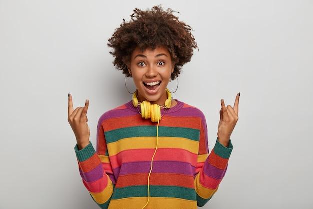 Ciemnoskóra kręcona kobieta pokazuje gest rock and rolla, lubi heavy metal, ma radosny wyraz twarzy, nosi sweter w paski