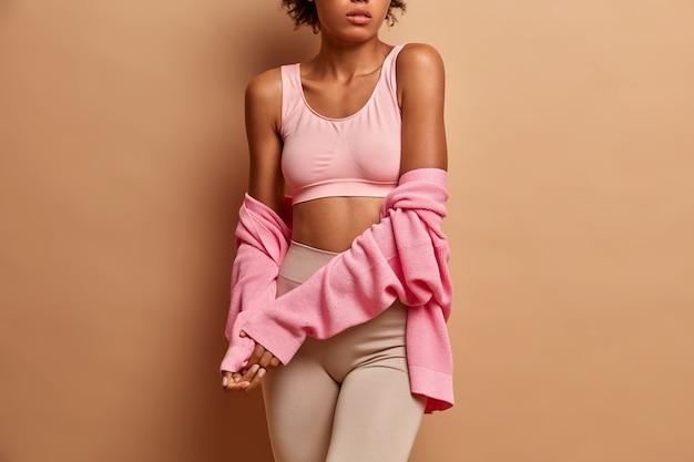 Ciemnoskóra modelka ma na sobie top i legginsy ze swetrem z długim rękawem