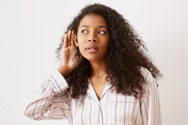 Ciemnoskóra nastolatka w piżamie trzymająca się za ucho i podsłuchująca. ładna afroamerykanka o ciekawym spojrzeniu, podsłuchiwaniu interesującej sekretnej rozmowy, z otwartymi ustami