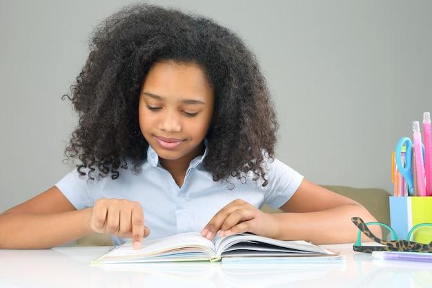 Ciemnoskóra uczennica czytająca książkę odrabiającą pracę domową. nauka w edukacji szkolnej