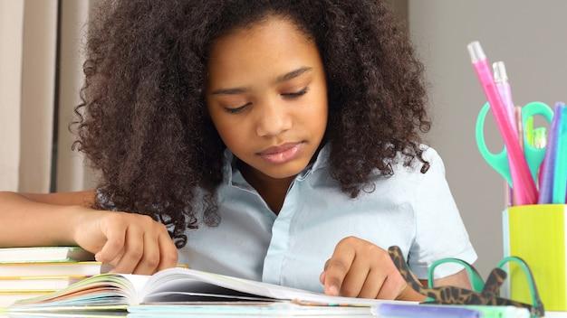 Ciemnoskóra uczennica czytająca książkę odrabiająca pracę domową