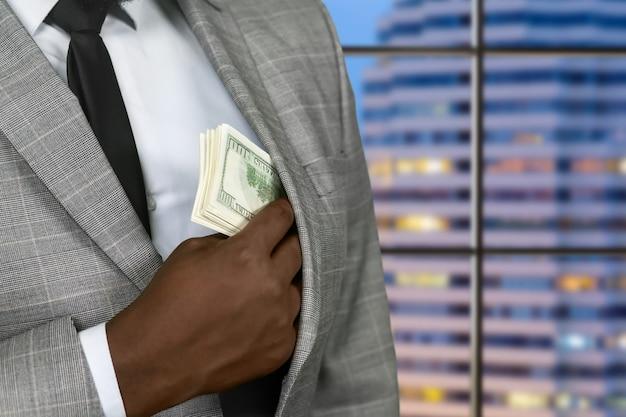 Ciemnoskóry biznesmen ukrywa dolary amerykańskie. bogaty urzędnik na tle wieczoru. właściciel luksusowego hotelu. człowiek musi zarabiać.