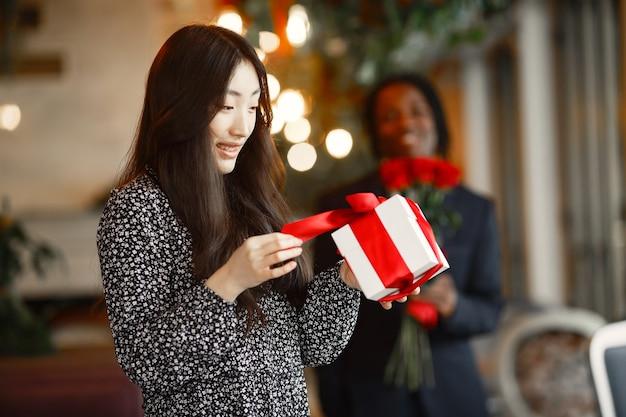 Ciemnoskóry facet z różami. szczęśliwa dziewczyna z prezentem. romantyczny wieczór w kawiarni.