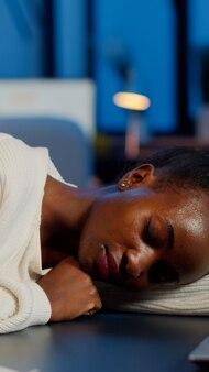 Ciemnoskóry freelancer zasypiający w godzinach nadliczbowych