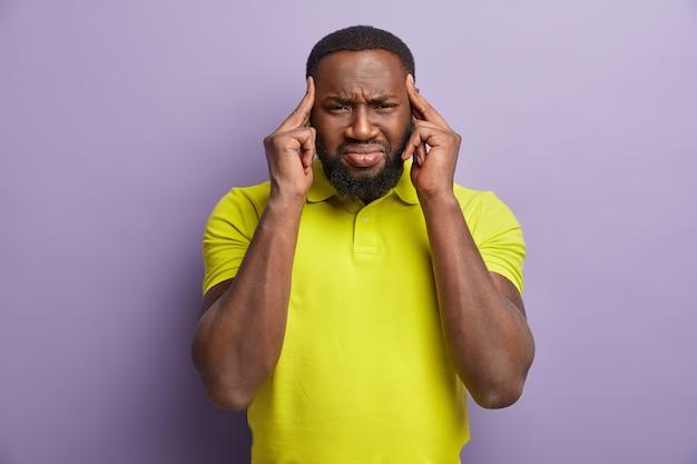 Ciemnoskóry mężczyzna dotyka skroni i ma izolowaną migrenę