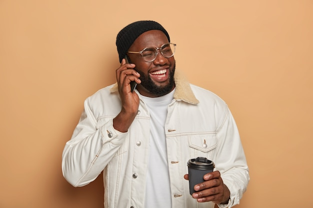 Ciemnoskóry mężczyzna prowadzi zabawną rozmowę telefoniczną, śmieje się podczas rozmowy telefonicznej