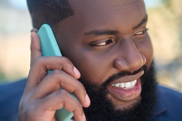 Ciemnoskóry mężczyzna w garniturze z telefonem w dłoni