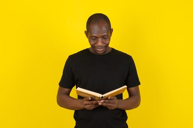 Ciemnoskóry młody mężczyzna czyta interesującą książkę na żółtej ścianie