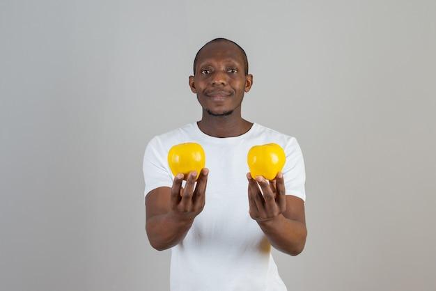Ciemnoskóry młody mężczyzna trzyma dojrzałe owoce pigwy na szarej ścianie
