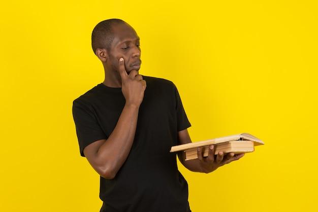 Ciemnoskóry młody mężczyzna trzymający książkę i myślący na żółtej ścianie