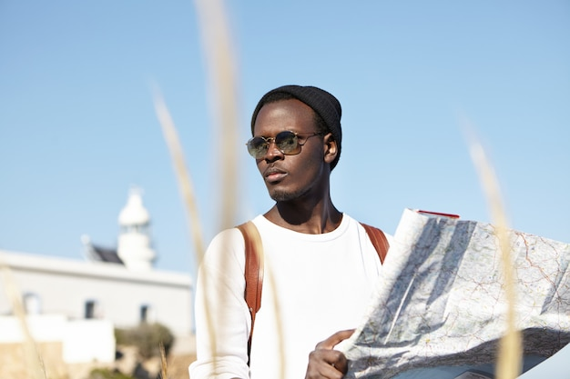 Ciemnoskóry podróżnik w modnych okularach przeciwsłonecznych i nakryciu głowy, studiujący papierową mapę w dłoniach, wyglądający na zmartwionego, zgubiony podczas podróży, ze skupioną miną, próbujący znaleźć właściwy kierunek