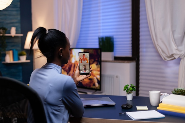 Ciemnoskóry przedsiębiorca rozmawiający z kolegami podczas wideokonferencji. zajęty pracownik przy użyciu nowoczesnych technologii sieci bezprzewodowej robi nadgodziny do pracy.