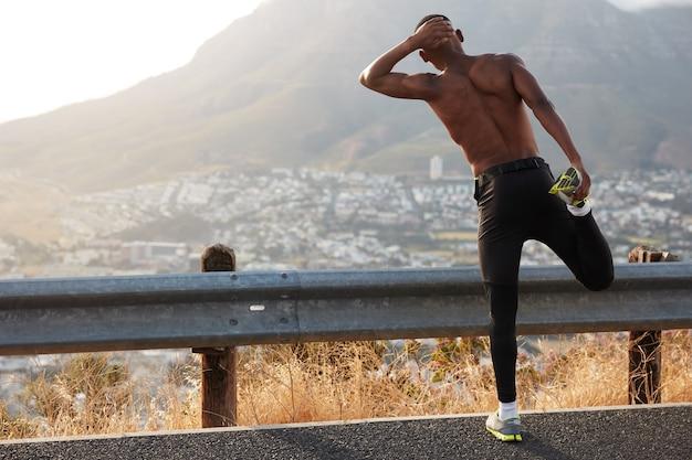 Ciemnoskóry samiec cofa się, wykonuje ćwiczenia rozciągające, podnosi nogi, podziwia piękne górskie widoki, trenuje, nosi trampki, stoi na asfalcie. wellness i fitness