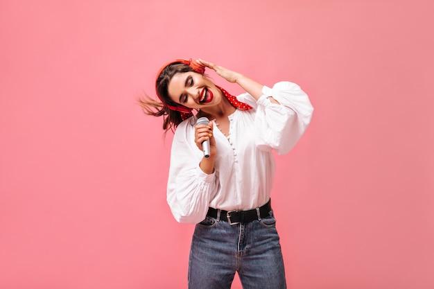 Ciemnowłosa dama w białej stylowej bluzce i dżinsach słucha piosenki w słuchawkach i śpiewa do mikrofonu na na białym tle.