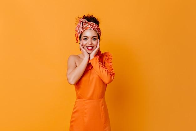 Ciemnowłosa dama z czerwoną szminką ubrana w pomarańczową sukienkę i na czele z uśmiechem patrząc na kamery na odosobnionej przestrzeni.