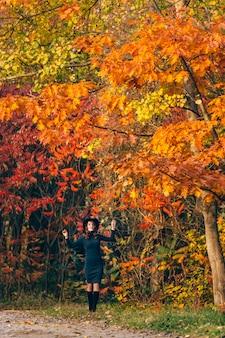 Ciemnowłosa dziewczyna w kapeluszu uśmiecha się i trzyma gałęzie drzew za ręce w parku jesienią