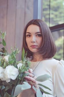 Ciemnowłosa dziewczyna z bukietem białych kwiatów