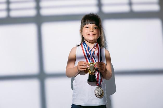 Ciemnowłosa dziewczyna z medalami mistrzostw sportowych i pucharem, stojąca w cieniu okna z zasłoniętą roletą. koncepcja sportu i zwycięstwa