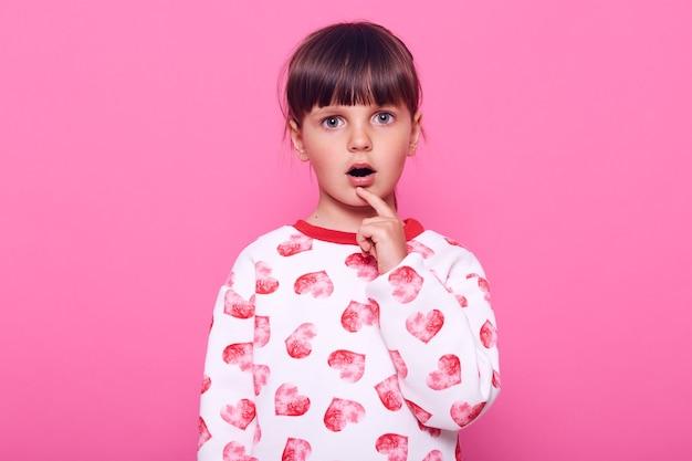 Ciemnowłosa dziewczynka z grzywką patrzy na aparat dużymi zdziwionymi oczami, trzyma palec na ustach, ubiera sweter, odizolowany na różowej ścianie.