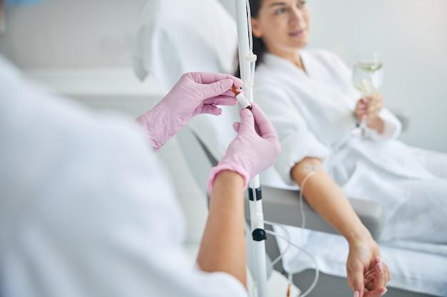 Ciemnowłosa klientka spa ze szklanką napoju w dłoni odwracająca wzrok podczas terapii dożylnej