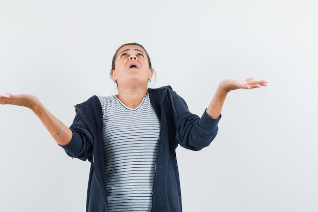 Ciemnowłosa kobieta pokazując bezradny gest w koszuli