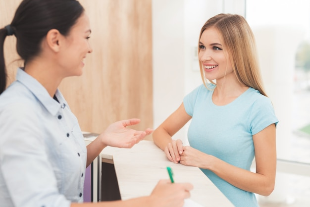 Ciemnowłosa kobieta pracuje w recepcji.